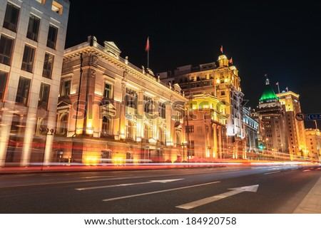 shanghai bund at night ,outstanding historical buildings with vehicle trails of light on the street .  - stock photo