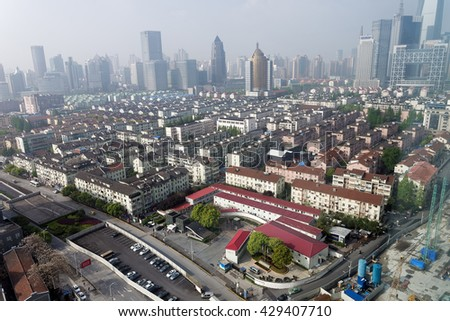 SHANGHAI, CHINA - April 16, 2016: Areal view of the Shanghai rooftops in the early foggy morning. Children are the most affected by poor Shanghai air quality, as they spend more time outdoors. - stock photo