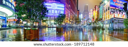 Shanghai, China - April 20, 2010: Nanjing Lu Road, night street after rain, wet pavement reflects light streetlights - stock photo