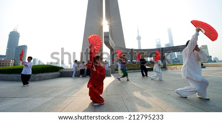 Shanghai, China - August 6, 2014: A beautiful view of Shanghai Skyline at sunrise with people doing Tai Chi.