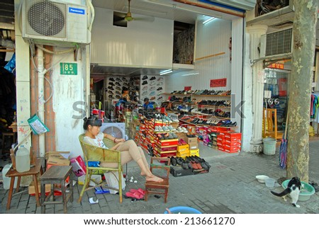 SHANGHAI, CHINA-AUGUST 24, 2013: lady running a shoes shop. The largest Chinese city by population has thousand of these shops. - stock photo