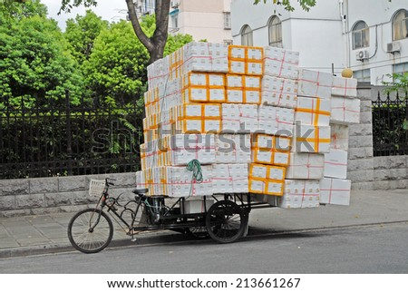 SHANGHAI, CHINA-AUGUST 19, 2013: typical tricycle transport. The largest Chinese city by population has thousand of these transports.