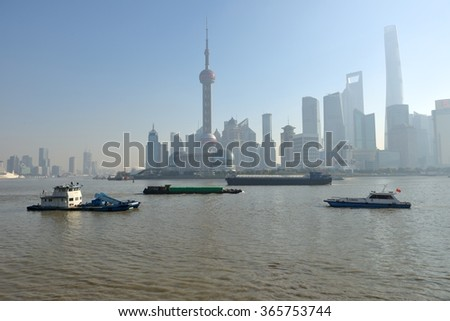Shanghai, China - December 22, 2014: A sunny morning, looking from the Bund toward Pu-dong New Area across Huangpu river, the river and modern skyscrapers are all veiled in light smog.