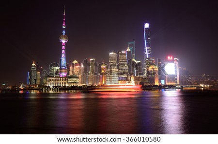 Shanghai, China - December 22, 2014: At night, the HuangPu River is lit up by cruise ships and by the lights of skyscrapers at Lujiazui Pudong New Area; it's a big tourist attraction of the city. - stock photo