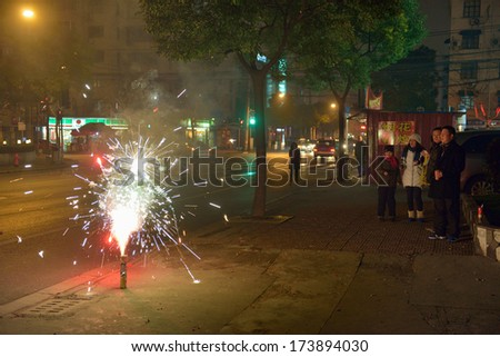 SHANGHAI, CHINA - FEBRUARY 09: Chinese family plays with fireworks in the street on February 09, 2013 in Shanghai. - stock photo