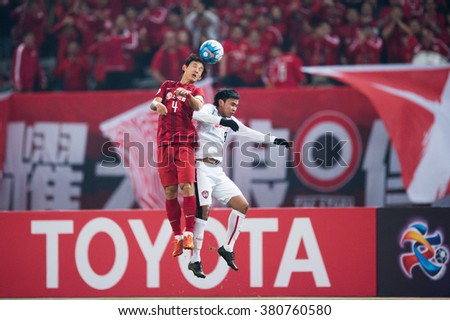 SHANGHAI-CHINA FEBRUARY 09:Wang Shenchao no.4 (red) of Shanghai SIPG in action during The AFC Champions League 2016 Playoff Shanghai SIPG and Muangthong Utd at Shanghai Stadium on Feb 09,2016 in China - stock photo