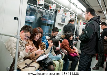SHANGHAI, CHINA - MARCH 21: Chinese people sits with mobile phones in Shanghai metro train on March 21, 2013 in Shanghai - stock photo