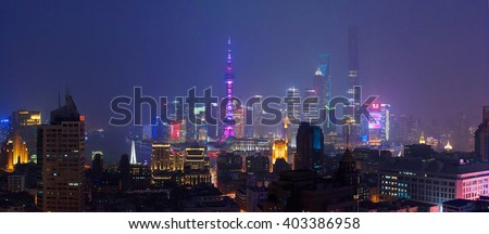 SHANGHAI, CHINA - MARCH 19, 2015: Famous Shanghai skyscrapers of Pudong financial district at night. Wide panorama shot from the roof of a building across the river.