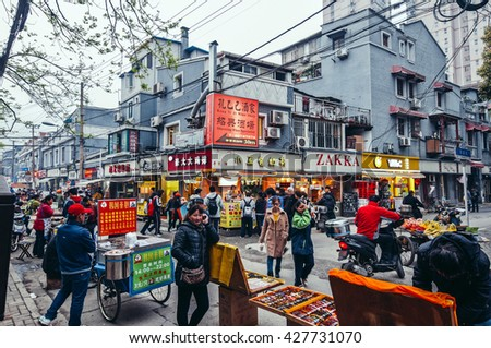 Shanghai, China - March 22nd, 2013: street sellers and walking people next to characteristic buildings in Old City of Shanghai area