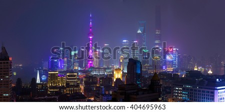 SHANGHAI, CHINA - MARCH 19, 2015: Shanghai financial district Pudong at night. Panorama shot from the roof of a building across the river.