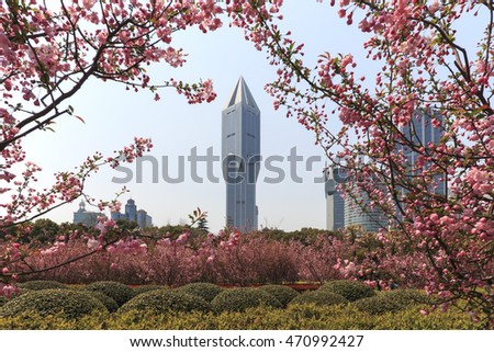 Shanghai, China - March 26, 2016: Tourists walking in People's Park one of the busiest in Shanghai. Tomorrow Square skyscraper on background