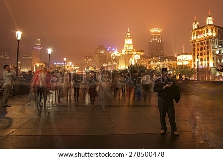 SHANGHAI, CHINA - MAY 2, 2015: Visitors on The Bund or Waitan at night during a foggy day. The Bund has dozens of historical buildings and is one of the most famous tourist destinations in Shanghai. - stock photo