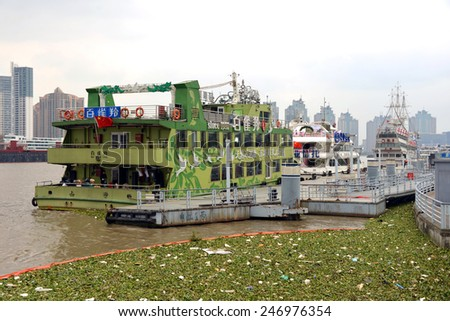 SHANGHAI, CHINA - NOV 9, 2014: Water Hyacinth corralled in Huangpu River of Shanghai and docked tour boats.  It is an invasive species and the problem has been compounded by the warm Autumn weather. - stock photo