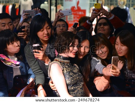 SHANGHAI, CHINA - NOVEMBER 10, 2014: Anne Hathaway poses for selfie with ecstatic fans at the red carpet for movie premiere of Interstellar at UME Theater in Shanghai, China - stock photo