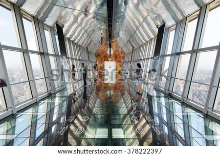 Shanghai, China - September 7, 2015: Tourists enjoy the breathaking view from the obvservatory floor of the Shanghai World Financial Center (SWFC) building, China.