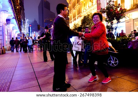 SHANGHAI, CN - MAR 17 2015:Elderly Chines couple dance at Nanjing Road. It is the main shopping street of Shanghai, China, and is one of the world's busiest shopping streets. - stock photo