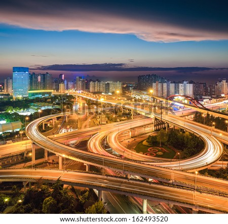 shanghai elevated road junction with sunset glow - stock photo