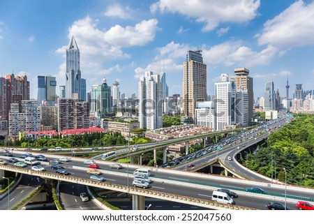 shanghai highway overpass with modern city skyline against a sunny sky , China