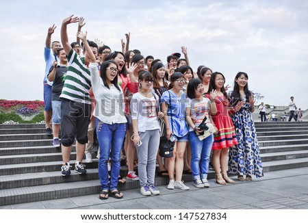SHANGHAI-JUNE 6. Cheerful Chinese tourist group. Shanghai wants develop tourism into strategic industry, create 300,000 jobs, contribute 8.5 percent to city's GDP by 2015. Shanghai, June 6, 2013.  - stock photo