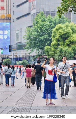 SHANGHAI-JUNE 5, 2014. Chinese woman takes a photo with a Canon Power-shot camera. The Power-Shot line has been successful for Canon, and is one of the best-selling digital camera lines worldwide. - stock photo