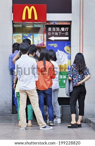 SHANGHAI-JUNE 5, 2014. Chinese youngsters lined up for McDonald's ice cream. McDonald's is the largest of fast food chain in the world. It has more than 33,000 outlets worldwide and 1800 in China.  - stock photo