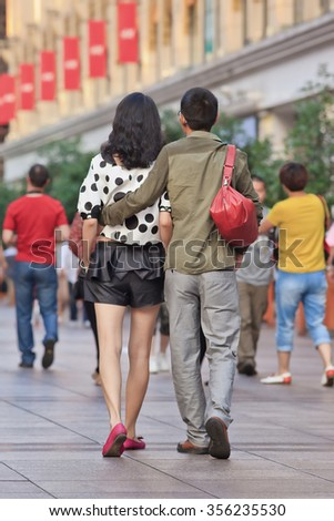 SHANGHAI-JUNE 5, 2014. Elegant couple walks in shopping area. Recent study showed divorce rate among middle-aged Chinese couples has risen last two decades, divorce rate among 20s couples has dropped. - stock photo
