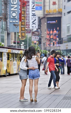 SHANGHAI-JUNE 4, 2014. Girls in Nanjing East Shopping Street take a photo with their smart phone. It is the main shopping street of Shanghai, and also one of the world's busiest shopping streets.  - stock photo