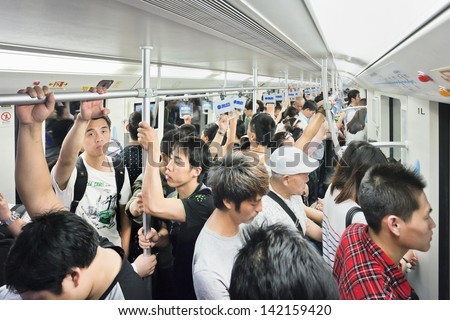 SHANGHAI-JUNE 6. Packed train car, subway. 12 metro lines and 287 stations, with an operating route length of 439 KM, making Shanghai the third longest metro in the world. Shanghai, June 6, 2013. - stock photo