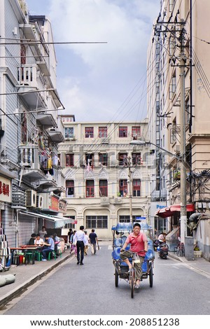 SHANGHAI-JUNE 5, 2014. Tricycle with water-tanks in a dense neighborhood. The recent estimate for the population of Shanghai is about 23,470,000, population density about 9,400 people per square mile. - stock photo