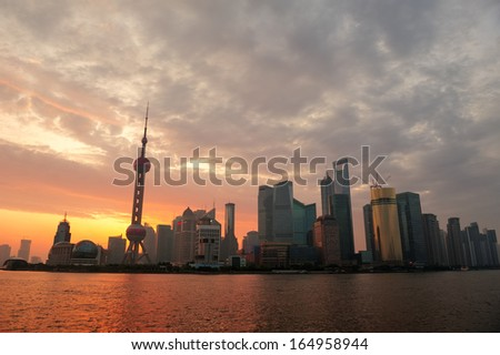 Shanghai morning city skyline silhouette over river with sunrise and Oriental Pearl Tower