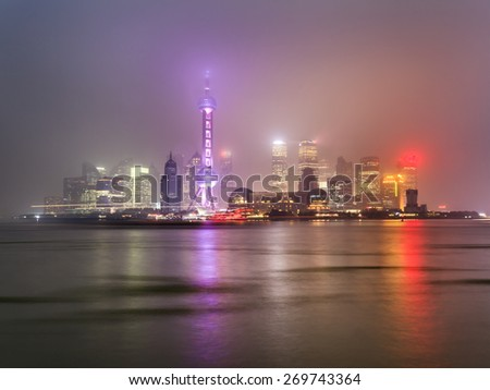 Shanghai's Pudong cityscape at sunset with bright illumination of modern buildings and towers reflecting in river waters - stock photo