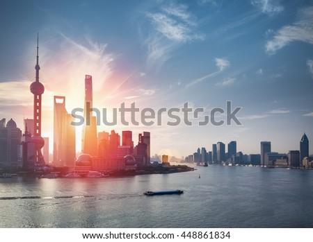 shanghai skyline against a blue sky with beautiful huangpu river - stock photo