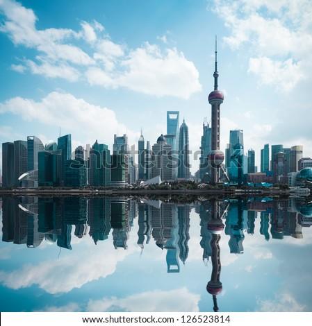 shanghai skyline against a blue sky with reflection - stock photo