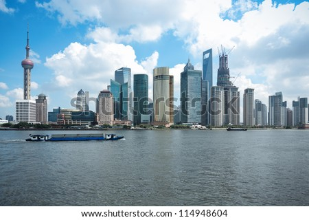 shanghai skyline at daytime with a cargo ship in huangpu river - stock photo