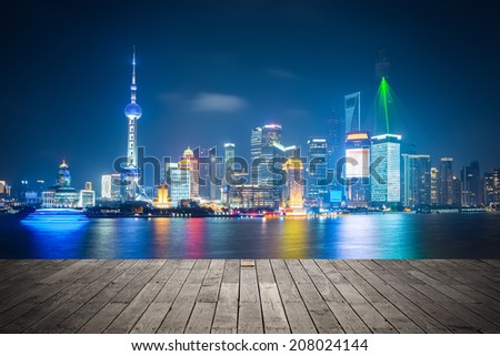 shanghai skyline at night , light show with wooden floor prospect  - stock photo