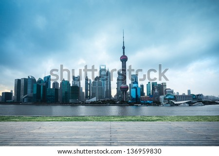 shanghai skyline in cloudy with wooden floor and lawn - stock photo