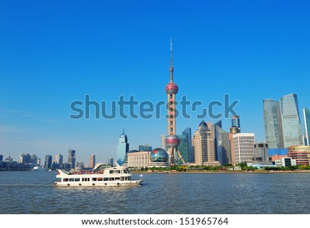 Shanghai skyline over river with boat