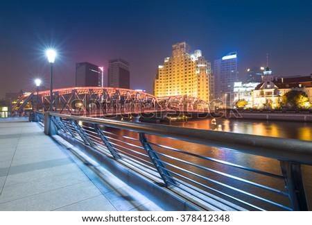 Shanghai Waibaidu bridge panorama at night with colorful light over river - stock photo