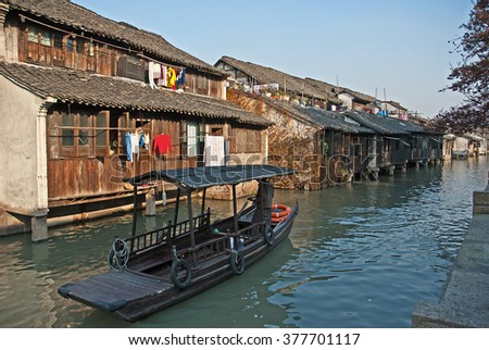 Shanghai, Wuzhen historic scenic town old houses and boat for tourists along a canal.