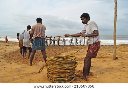 SHANGHUMUGHAM, TRIVANDRUM, KERALA, INDIA - MARCH 30, 2014: Fishermen hauling their catch still trapped in the fishing net. Visitors to the beach lend a helping hand. - stock photo
