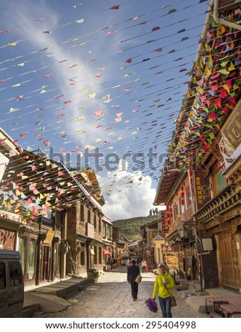 SHANGRI LA, CHINA, JUNE 24, 2015: Prayer flags decorate in old town. People are walking through the historical old town in chinese city shangri-la alias zhongdian , Yunnan China. - stock photo