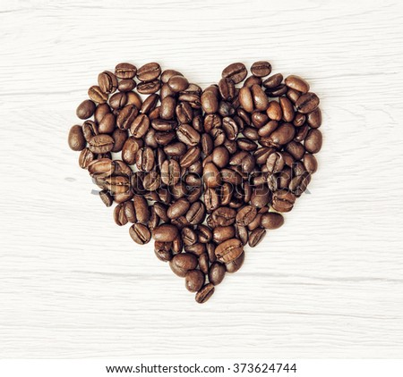 Shape heart of the coffee beans on the wooden background. Valentine's Day. Symbol of love. - stock photo
