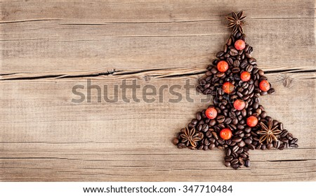 Shape of christmas tree made of coffee beans on wooden table. Top view, copy space. Winter holidays concept