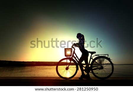Shape of the beautiful young woman with bicycle on sunrise near a sea - stock photo