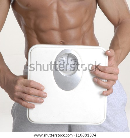 Shaped and fitness man holding a weight scale.