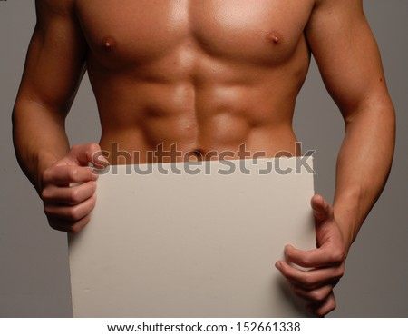 Shaped and healthy body man holding a white panel,,shaped abdominal, - stock photo