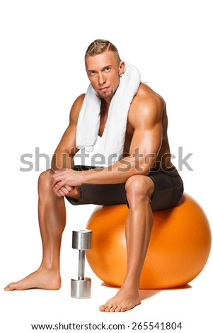 Shaped and healthy body man with a white towel around his neck sitting on fitness ball isolated on white background - stock photo