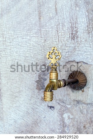 shaped bronze on the wall and a jet of water - stock photo