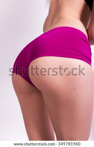 Shapely ass of a young girl in purple shorts - stock photo