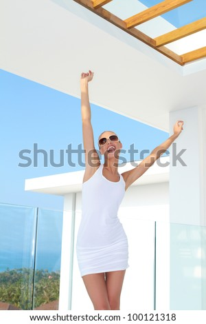 Shapely woman in skimpy mini skirt and dark glasses standing on an outdoor summer patio raising her arms in jubilation - stock photo